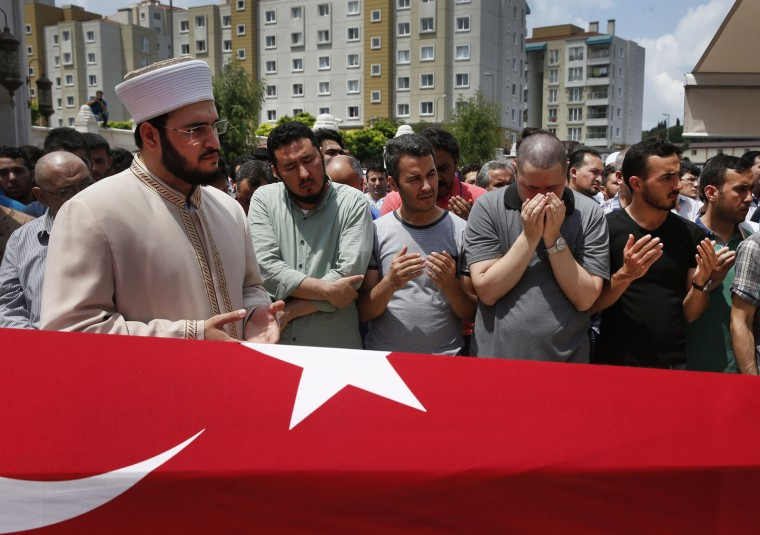 An imam read prayers as relatives mourn as they gather around the Turkish flag-draped coffin of Habibullah Sefer, one of the victims killed Tuesday at the blasts in Istanbul's Ataturk airport, during the funeral in Istanbul, Thursday, June 30, 2016. Suicide attackers killed dozens and wounded scores of others at the busy airport late Tuesday, the latest in a series of bombings to strike Turkey in recent months. Turkish authorities have banned distribution of images relating to the Ataturk airport attack within Turkey. (AP Photo/Lefteris Pitarakis)