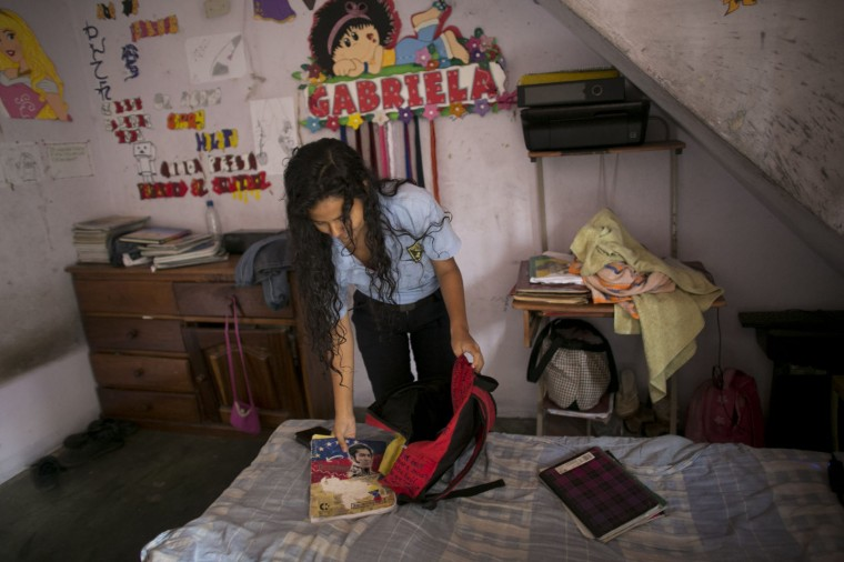 "In this June 1, 2016, Maria Arias packs her backpack in her bedroom, decorated with her middle name ""Gabriela,"" in Caracas, Venezuela. Chatty and so studious her classmates call her ""Wikipedia,"" Arias started the year at a school with dreams of becoming an accountant and moving to Paris. Her parents saved up to buy her new notebooks, one for each subject, but nine months later, they remain mostly empty due to her teachers not showing up for class, or entire school days being cancelled. (AP Photo/Ariana Cubillos)"