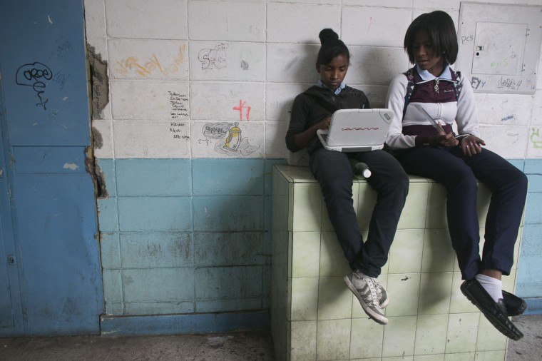 In this May 31, 2016 photo, a student uses a government provided laptop as she and a classmate wait in the hallway for a class to start at their public high school in Caracas, Venezuela. The late President Hugo Chavez made education a centerpiece of his socialist revolution, using the riches from a historic boom in the price of oil to train teachers and distribute free laptops, but in just a few years, all of that progress has been undone. (AP Photo/Ariana Cubillos)