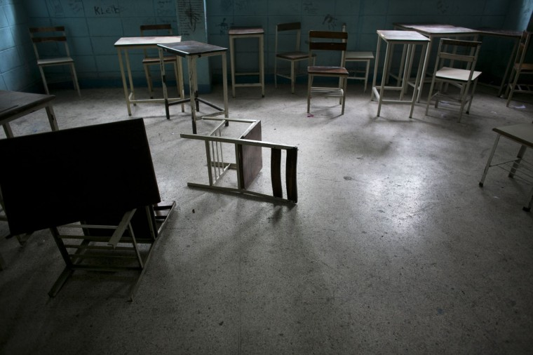 In this June 1, 2016 photo, desks and chairs sit in an abandoned classroom at a public high school in Caracas, Venezuela. Officially, Venezuela canceled 16 school days this year, including Friday classes because of an energy crisis. In reality, Venezuelan children are now missing an average of 40 percent of class time, a parent group estimates, and a third of teachers skip work on any given day to wait in food lines. (AP Photo/Ariana Cubillos)