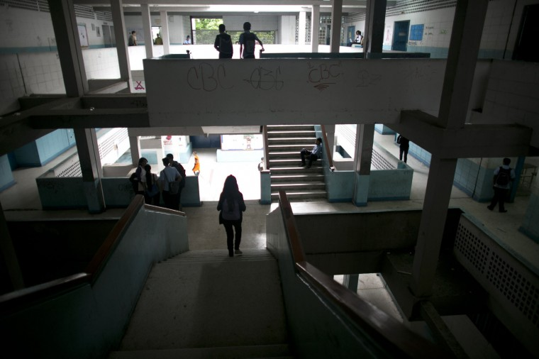 In this June 1, 2016 photo, students walk inside their public high school in Caracas, Venezuela. While the school locks its gate each morning, armed robbers still manage to infiltrate and stick up kids between classes. (AP Photo/Ariana Cubillos)