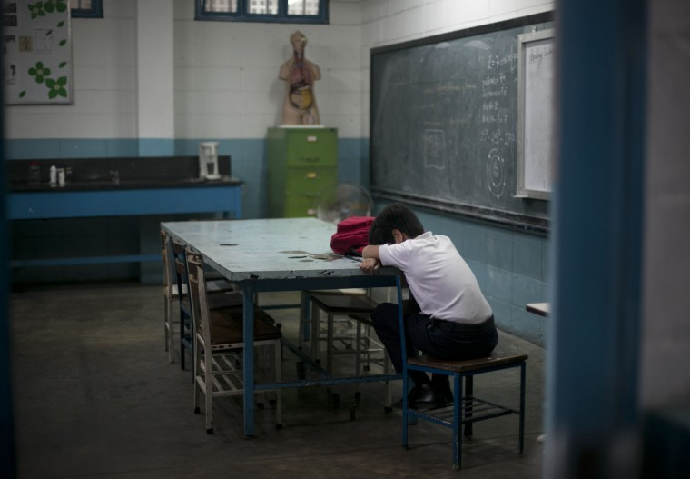 In this June 1, 2016 photo, a student lays his head down during class at a public high school in Caracas, Venezuela. The annual high school dropout rate has doubled to 11 percent since 2011 and schools are understaffed as professionals flee the country. (AP Photo/Ariana Cubillos)
