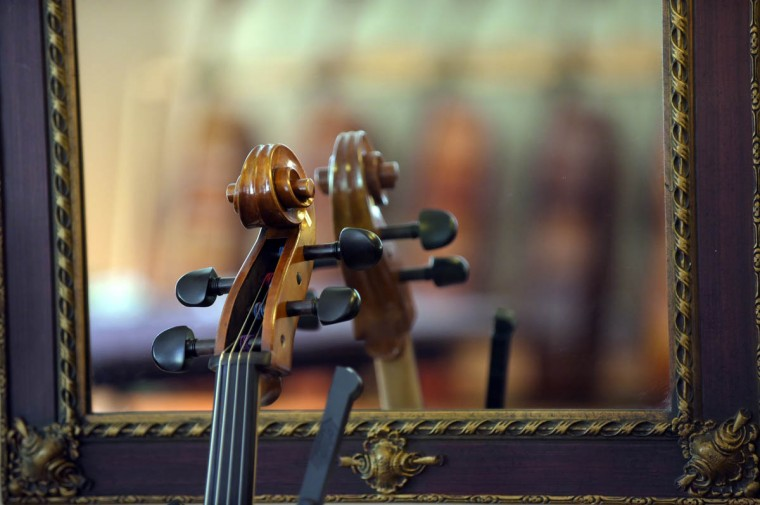 A cello scroll is reflected in a mirror in one of the showrooms. Performance venues and education of the craftsmen at Perrin & Associates Fine Violins range from MICA and the Peabody Conservatory to musical institutions in Boston, London and Glasgow. (Algerina Perna/Baltimore Sun)
