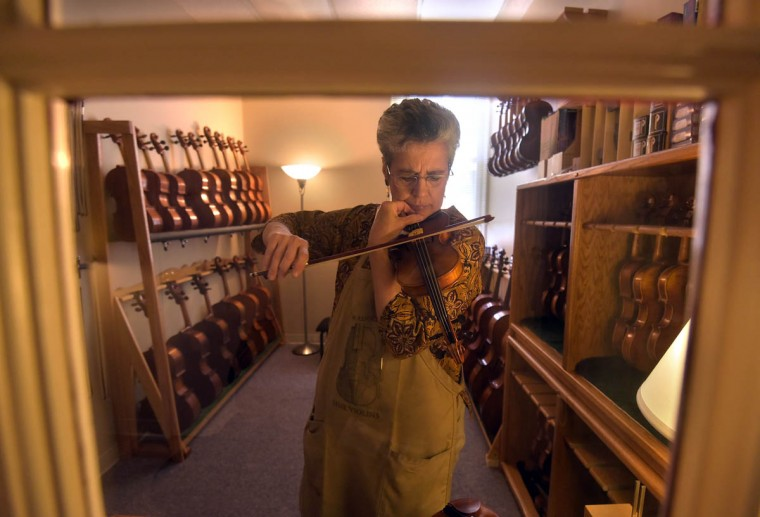 Carolyn Foulkes tunes small violins in preparation for a 7-year-old customer who will be renting a violin this summer from Perrin & Associates Fine Violins. (Algerina Perna/Baltimore Sun)