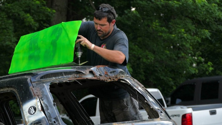 Kevin Greenway of Rising Sun attaches a plate with his vehicle's number to its roof during Demo Derby Day at Arcadia Volunteer Fire Company's carnival grounds. (Karl Merton Ferron/Baltimore Sun)