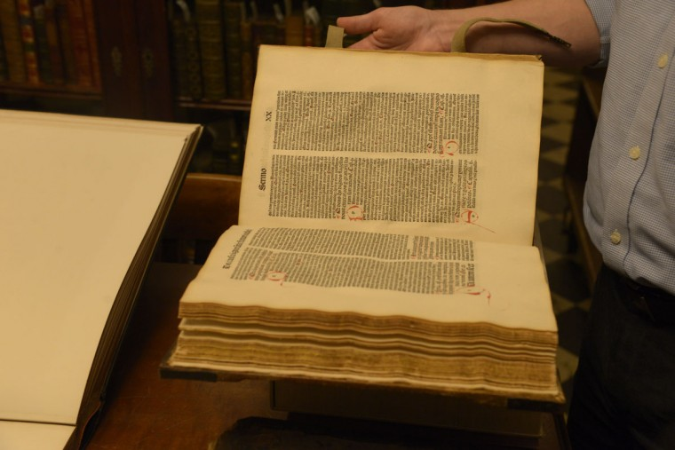 "One of the oldest printed books in the collection, this religious manuscript from 1489 still has the original chain that would have connected it to a monastery desk in Europe. ""You would come in and you could open it up and you could take a look at it,"" says curator Paul Espinosa, ""But it was chained to the desk because they didn't want it to go missing."" Since the Peabody Library first opened, all of the books in the collection have been non-circulating, available for reference only. (Christina Tkacik/Baltimore Sun)"