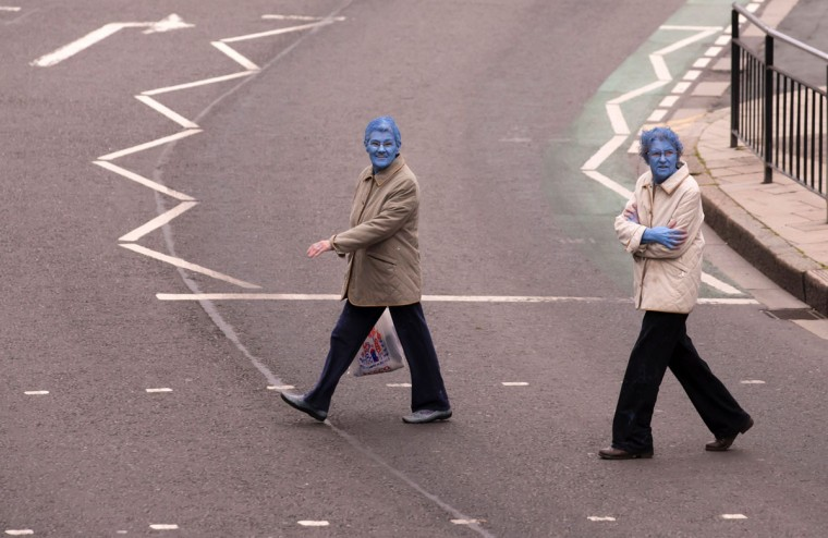 "After taking part in Spencer Tunick's ""Sea of Hull"" installation, two women cross the road in Kingston upon Hull on July 9, 2016. Over a period of 20 years, the New York based artist has created over 90 art installations in some of the most culturally significant places and landmarks around the world including the Sydney Opera House, Place des Arts in Montreal, Mexico City, Ernest Happel Stadium in Vienna and Munich in Germany. / (AFP PHOTO / JON SUPER)"