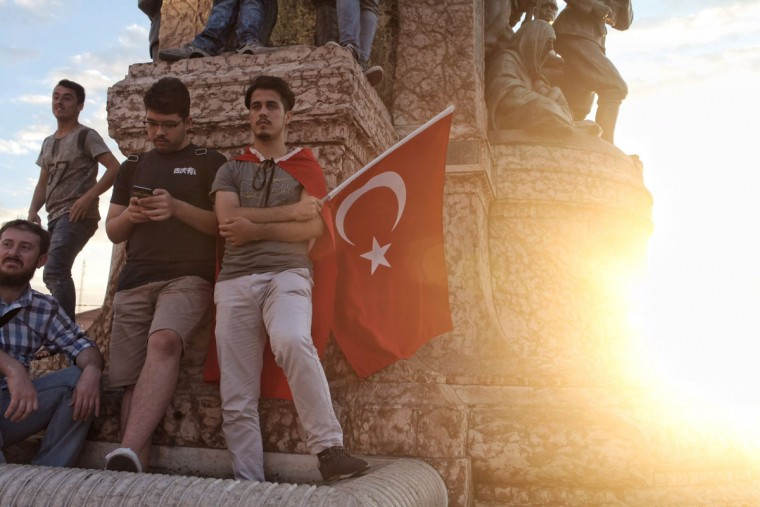 ISTANBUL, TURKEY - JULY 18: Supporters of Turkish President Recep Tayyip Erdogan stand in front of a statue of Mustafa Kemal Ataturk, founder of modern Turkey, with a Turkish soldier and a Turkish woman in the Independence War, as part of a monument located in central Taksim square on July 18, 2016 in Istanbul, Turkey. Clean up operations are continuing in the aftermath of Friday's failed military coup attempt which claimed the lives of more than 208 people. In raids across Turkey 7,543 people have been arrested in relation to the failed coup including high-ranking soldiers and judges, Turkey's Prime Minister Binali Yildirim has said. (Photo by Kursat Bayhan/Getty Images)