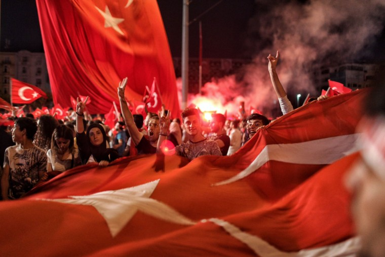 ISTANBUL, TURKEY - JULY 18: Supporters of Turkish President Tayyip Erdogan wave flags as they gather in Istanbul's central Taksim Square on July 18, 2016 in Istanbul, Turkey. Clean up operations are continuing in the aftermath of Friday's failed military coup attempt which claimed the lives of more than 208 people. In raids across Turkey 7,543 people have been arrested in relation to the failed coup including high-ranking soldiers and judges, Turkey's PM Binali Yildirim has said. (Photo by Kursat Bayhan/Getty Images)