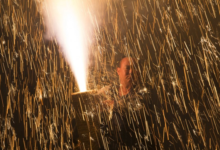 A pyrotechnician holds a bamboo cylinder containing fireworks as he performs 'tezutsu hanabi' or hand held fireworks at the Yoshida Shrine on July 15, 2016 in Toyohashi, Japan. The firework event was held as part of Toyohashi city's annual Gion Festival, which has 460 years history in the central Japanese region. (Photo by Tomohiro Ohsumi/Getty Images)