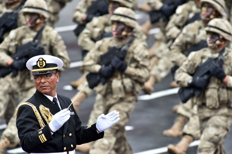 A Peruvian Navy band leader conducts while troops march during a military parade during Independence Day celebrations in Lima on July 29, 2016. / (AFP Photo/Cris Bouroncle)