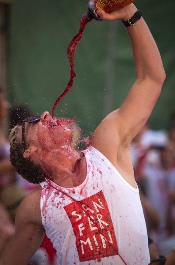 A reveller drinks wine as he celebrates the 'Chupinazo' (start rocket) to mark the kickoff at noon sharp of the San Fermin Festival, in front of the Town Hall of Pamplona, northern Spain, on July 6, 2016. The San Fermin festival is a symbol of Spanish culture that attracts thousands of tourist to watch the bull runs despite heavy condemnation from animal rights groups. / (AFP Photo/Miguel Riopa)