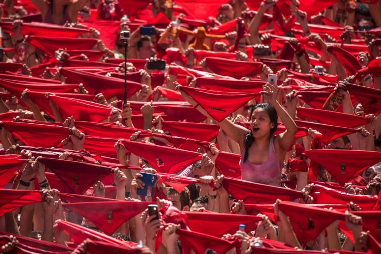 Participants hold red scarves as they celebrate the 'Chupinazo' (start rocket) to mark the kickoff at noon sharp of the San Fermin Festival, in front of the Town Hall of Pamplona, northern Spain, on July 6, 2016. The San Fermin festival is a symbol of Spanish culture that attracts thousands of tourist to watch the bull runs despite heavy condemnation from animal rights groups. / (AFP Photo/Pedro Armestre)