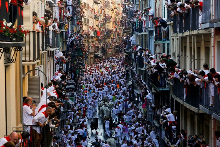 Revellers run with Fuente Ymbro's fighting bulls along Estafeta Street during the second day of the San Fermin Running of the Bulls festival on July 7, 2016 in Pamplona, Spain. The annual Fiesta de San Fermin, made famous by the 1926 novel of US writer Ernest Hemmingway entitled 'The Sun Also Rises', involves the daily running of the bulls through the historic heart of Pamplona to the bull ring. (Photo by Pablo Blazquez Dominguez/Getty Images)
