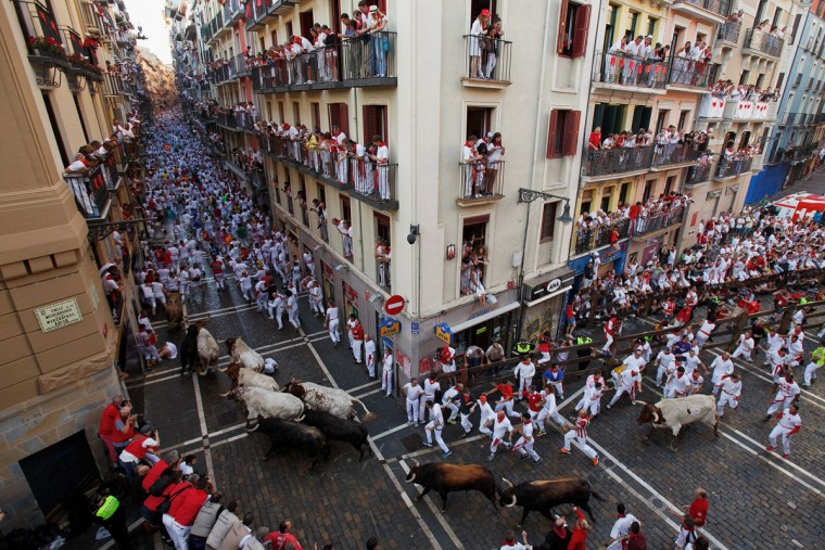 Revellers run with Fuente Ymbro's fighting bulls entering Estafeta Street during the second day of the San Fermin Running of the Bulls festival on July 7, 2016 in Pamplona, Spain. The annual Fiesta de San Fermin, made famous by the 1926 novel of US writer Ernest Hemmingway entitled 'The Sun Also Rises', involves the daily running of the bulls through the historic heart of Pamplona to the bull ring. (Photo by Pablo Blazquez Dominguez/Getty Images)