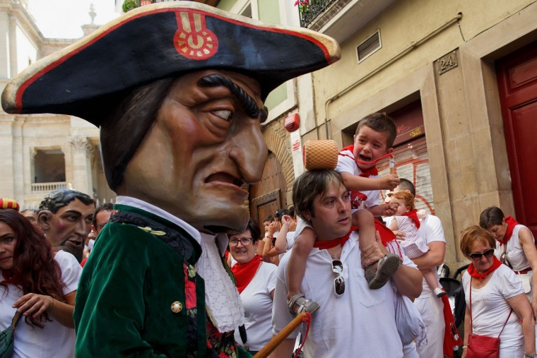 A child react (R) as Caravinagre 'Vinegar face' kiliki (C) approaches during the Comparsa de Gigantes y Cabezudos, or Giants and Big Heads parade on the third day of the San Fermin Running of the Bulls festival on July 8, 2016 in Pamplona, Spain. The annual Fiesta de San Fermin, made famous by the 1926 novel of US writer Ernest Hemmingway entitled 'The Sun Also Rises', involves the daily running of the bulls through the historic heart of Pamplona to the bull ring. (Photo by Pablo Blazquez Dominguez/Getty Images)