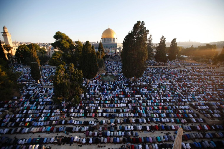 Palestinian Muslim men perform the morning Eid al-Fitr prayer near the Dome of Rock at the Al-Aqsa Mosque compound, Islam's third most holy site, in the old city of Jerusalem on Wednesday. Muslims worldwide celebrate Eid al-Fitr marking the end of the fasting month of Ramadan. (AHMAD GHARABLI/AFP/Getty Images)