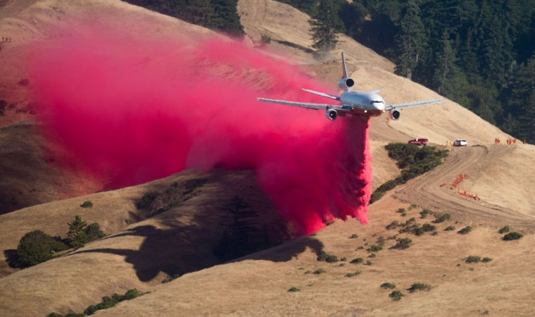 A plane drops fire retardant while battling the Soberane Fire in Carmel Highlands, California on July 23, 2016. The fire has scored more than 10,000 acres and threatens 1,650 structures according to Cal Fire. (AFP PHOTO / NOAH BERGER)