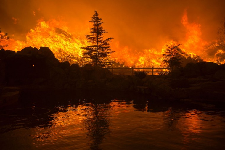 Flames are reflected in a backyard swimming pool at the Sand Fire on July 23 2016 near Santa Clarita, California. Fueled by temperatures reaching about 108 degrees fahrenheit, the wildfire began yesterday has grown to 11,000 acres. (AFP PHOTO / DAVID MCNEW)