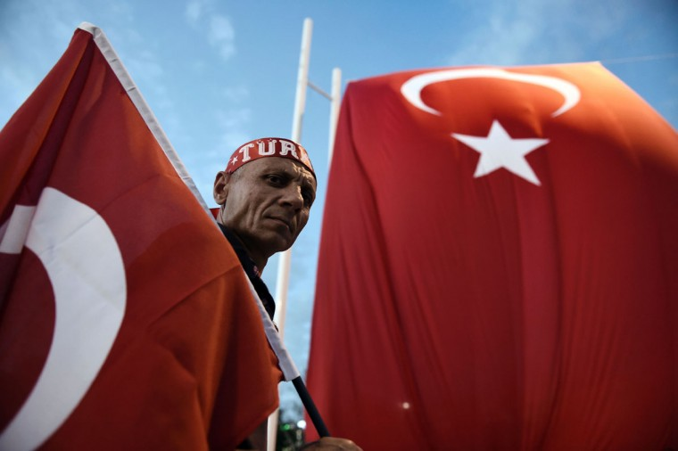 A Pro-Erdogan supporter holds a Turkish national flag as he looks on during a rally at Taksim square in Istanbul on July 18, 2016 following the military failed coup attempt of July 15. Turkish security forces on July 18 carried out new raids against suspected plotters of the botched coup against the rule of President Recep Tayyip Erdogan, as international concern grew over the scale of the crackdown. Thousands of pro-Erdogan supporters waving Turkish flags filled the main Kizilay Square in Ankara while similar scenes were seen in Taksim Square in Istanbul, AFP photographers said. (AFP PHOTO / ARIS MESSINIS)
