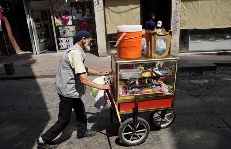 A street seller pushes his cart as people go on with their daily life on July 18, 2016 in the Kasimpasa neighborhood in Istanbul where Turkish President Recep Tayyip Erdogan was born. In the town where Turkish President Recep Tayyip Erdogan grew up, life had returned to normal with children playing in the streets, families escaping the hot summer sunshine and friends sipping tea in cafes. No one could guess that the army attempted a coup on July 15 and that Erdogan had faced the biggest fight of his long political career. Only the presence of more Turkish flag, swaying in the gentle summer breeze, were evidence of the last events. (AFP PHOTO / DANIEL MIHAILESCU)