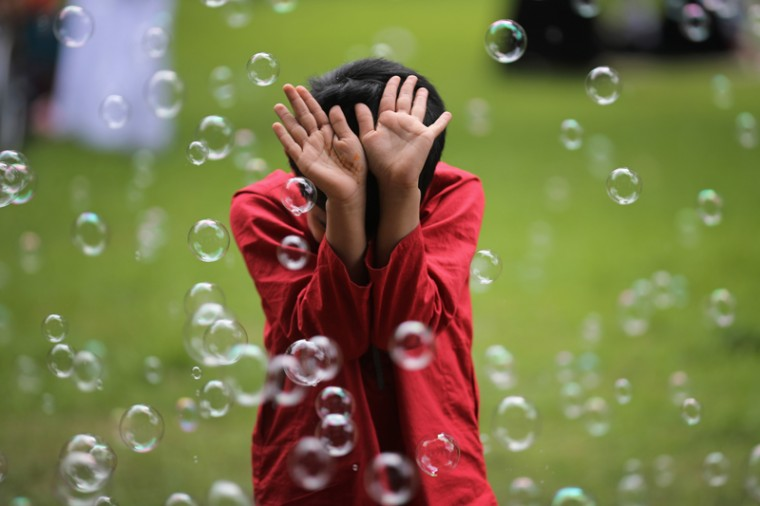 A young boy plays with soap bubbles as the Birmingham Muslim community celebrates the festival of Eid in Small Heath Park on Wednesday in Birmingham, England. Up to 70,000 people congregated in Small Heath Park to celebrate the Muslim holiday of Eid, which marks the end of 30 days of dawn-to-sunset fasting during the holy month of Ramadan.  (Christopher Furlong/Getty Images)