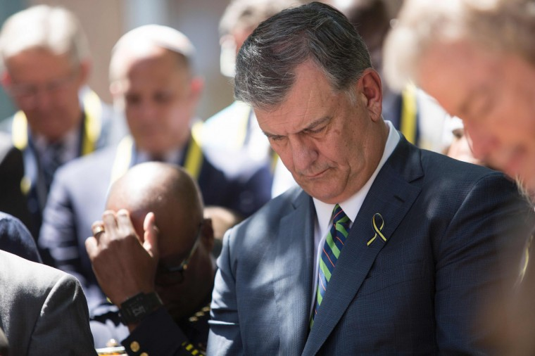 Dallas Mayor Mike Rawlings bows his head in prayer during a vigil in Thanks-Giving Square in Dallas, Texas, on July 8, 2016, following the shootings during a peaceful protest on July 7 which left 5 police officers dead. (Laura Buckman/AFP/Getty Images)