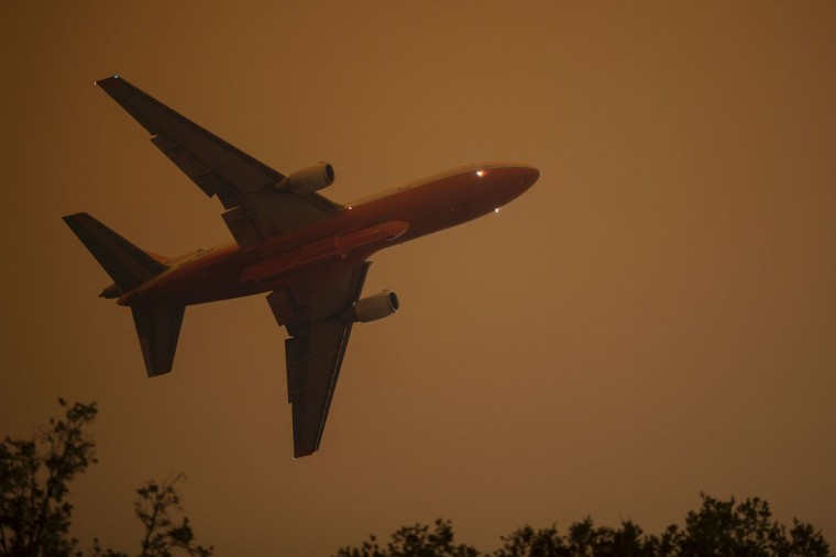 A firefighting DC-10 912 flies low over homes at the Sand Fire on July 23 2016 near Santa Clarita, California. Fueled by temperatures reaching about 108 degrees fahrenheit, the wildfire began yesterday has grown to 11,000 acres. (AFP PHOTO / DAVID MCNEW)