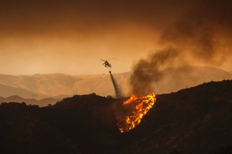 A firefighting helicopter drops water at the Sand Fire on July 23 2016 near Santa Clarita, California. Fueled by temperatures reaching about 108 degrees fahrenheit, the wildfire began yesterday has grown to 11,000 acres. (AFP PHOTO / DAVID MCNEW)