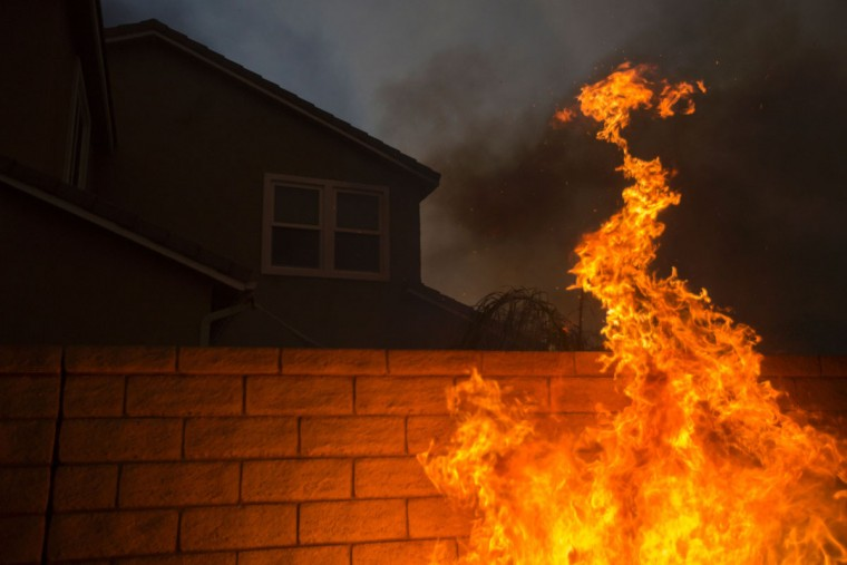 Flames lap at the wall of a home at the Sand Fire on July 23 2016 near Santa Clarita, California. Fueled by temperatures reaching about 108 degrees fahrenheit, the wildfire began yesterday has grown to 11,000 acres. (AFP PHOTO / DAVID MCNEW)