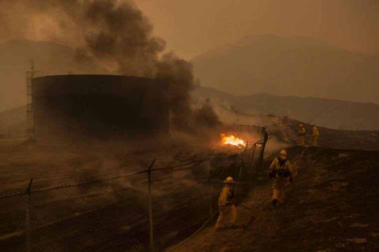 Firefighters hose down burning pipes near a water tank at the Sand Fire on July 23 2016 near Santa Clarita, California. Fueled by temperatures reaching about 108 degrees fahrenheit, the wildfire began yesterday has grown to 11,000 acres. (AFP PHOTO / DAVID MCNEW)
