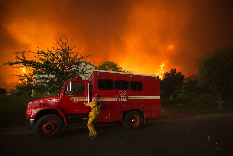 A firefighter reaches for the door of his truck as flames close in on homes at the Sand Fire on July 23 2016 near Santa Clarita, California. Fueled by temperatures reaching about 108 degrees fahrenheit, the wildfire began yesterday has grown to 11,000 acres. (AFP PHOTO / DAVID MCNEW)
