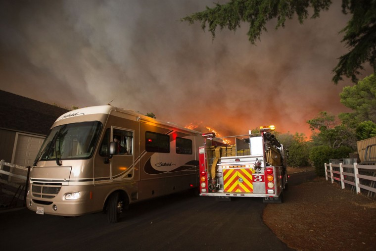 A resident flees in a motor home as flames close in at the Sand Fire on July 23 2016 near Santa Clarita, California. Fueled by temperatures reaching about 108 degrees fahrenheit, the wildfire began yesterday has grown to 11,000 acres. (AFP PHOTO / DAVID MCNEW)