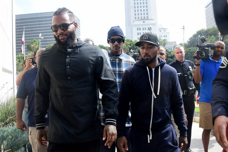 Rappers The Game (L) and Snoop Dogg (C) make their way into LAPD headquarters on July 8, 2016, after they led a peaceful demonstration outside a Los Angeles Police Department recruit graduation ceremony in what they called an effort to promote unity in the aftermath of the deadly shootings of police officers in Dallas. (Frederic J. Brown/AFP/Getty Images)