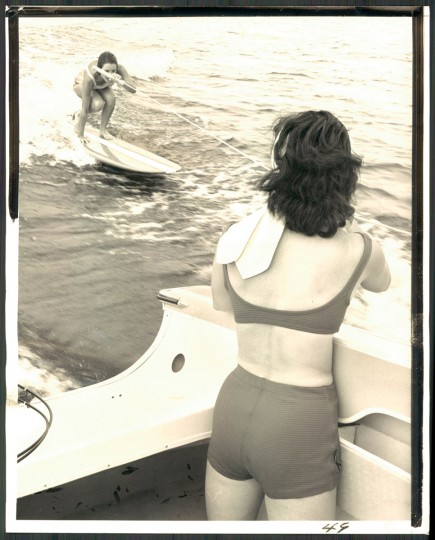 """Once the surfer is upright, she adjusts her feet on the board to maneuver it into the right position on the face of wake."" July 6, 1964. (Baltimore Sun)"