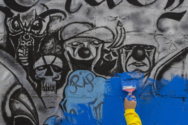 In this June 21, 2016 photo, an inmate paints over Mara Salvatrucha gang graffiti in the April 22 neighborhood in Soyapango, El Salvador. After becoming the world's murder capital last year and posting an equally bloody start to 2016, El Salvador has seen its monthly homicide rates fall by about half. The government attributes the drop to a tough military crackdown on the country's powerful gangs, while the gangs themselves claim credit for a nonaggression pact between the three biggest criminal groups. (AP Photo/Salvador Melendez)