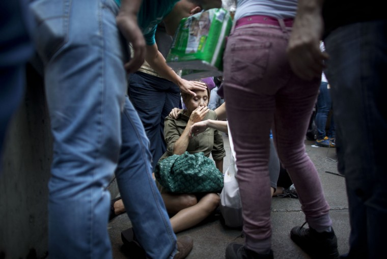 In this May 5, 2016 photo, Irama Carrero is aided by fellow shoppers after fainting in a food line outside a grocery store, in the afternoon in Caracas, Venezuela. Carrero, who said she hadn't eaten that day, had spent hours staring blankly ahead in the line for the elderly when her gaze suddenly became more fixed. She tilted backward and no one broke her fall. Her head smacked the concrete and when she came to she started vomiting. (AP Photo/Ariana Cubillos)