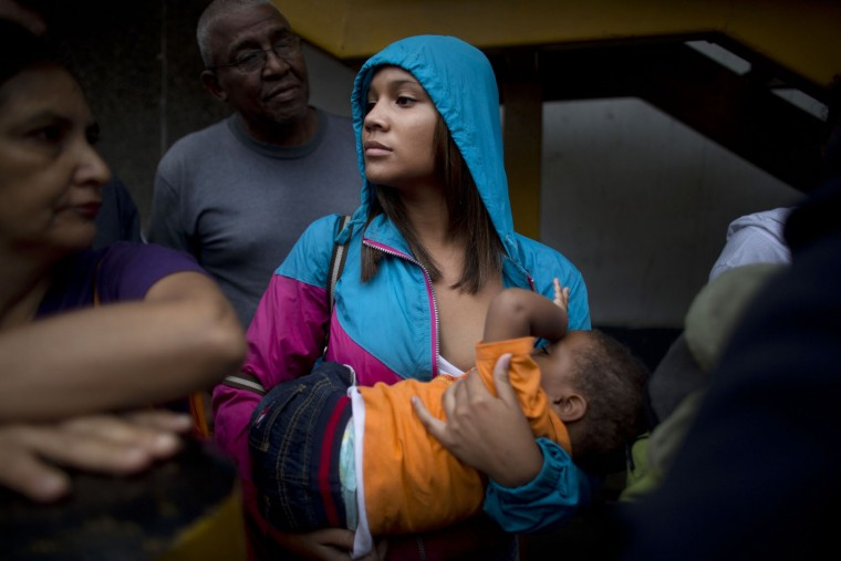 In this Tuesday, May 3, 2016 photo, Madeley Vasquez, 16, breast feeds her one-year-old son Joangel as she waits in line outside a supermarket to buy food in Caracas, Venezuela. Vasquez once ran down the block to avoid getting caught up in a knife fight that broke out when a woman was accused of cutting the line. (AP Photo/Ariana Cubillos)