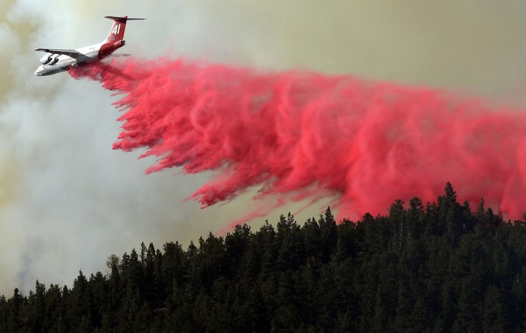 A trail of slurry is deposited by a bomber while fighting the Cold Springs Nederland fire in Colorado on Saturday July 9, 2016. (Paul Aiken/Boulder Daily Camera via AP)