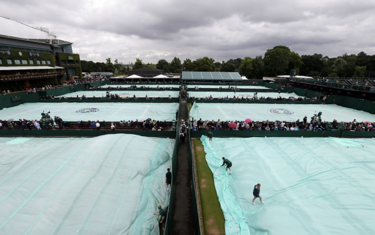 Members of the ground staff remove the covers from the courts as rain delays play on day five of the Wimbledon Tennis Championships in London, Friday, July 1, 2016. (AP Photo/Tim Ireland)