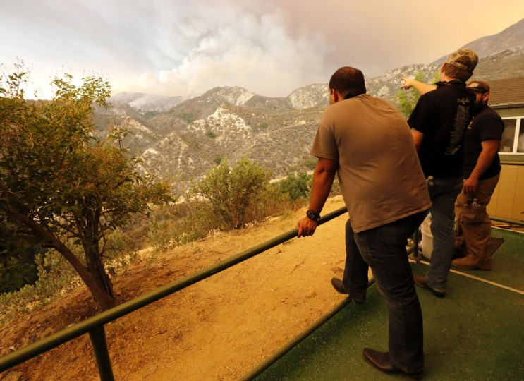 Wildlife Waystation volunteers watch the Sand Fire burn near their facility in Santa Clarita, Calif., on Saturday, July 23, 2016. A wildfire burning in the mountainous Angeles National Forest north of Los Angeles has grown to more than 17 square miles. Judy says the Wildlife Waystation, a private sanctuary for rescued exotic animals, is being evacuated. The Wildlife Waystation has about 400 animals on 160 acres within the national forest. (Katharine Lotze/The Santa Clarita Valley Signal via AP)