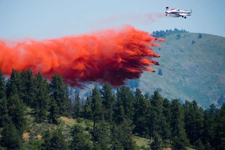 A plane spreads flame retardant as they battle the Cold Springs Fire near Nederland, Colo. on Sunday, July 10, 2016. (Autumn Parry/The Daily Camera via AP)