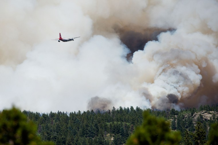 A plane approaches the Cold Springs Fire as the fire spread rapidly due to heavy winds in Nederland, Colo. on Sunday, July 10, 2016. (Autumn Parry/Boulder Daily Camera via AP)