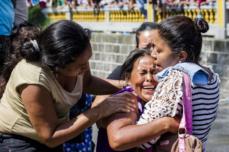 A relative of an inmate is comforted as more than a thousand inmates are bused out of the Cojutepeque prison in El Salvador, Thursday, June 16, 2016. This prison, which houses more than a thousand 18th street imprisoned gang members, will be closed down by the government, since it has been unable to prevent the amount of illegal activities happening inside the prison walls. Inmates will be relocated to other medium-security prisons. (AP Photo/Salvador Melendez)