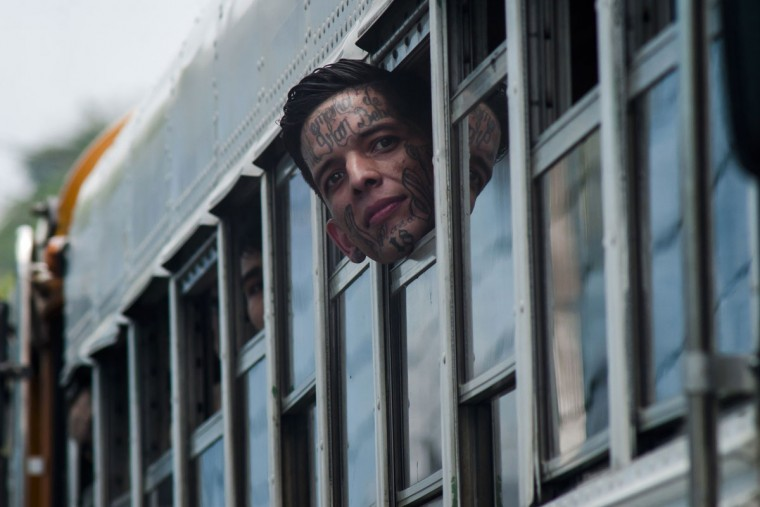 An inmate peers from the window of a bus as it rides out of the Cojutepeque prison in El Salvador, Thursday, June 16, 2016. This prison, which houses more than a thousand 18th street imprisoned gang members, will be closed down by the government, since it has been unable to prevent the amount of illegal activities happening inside the prison walls. Inmates will be relocated to other medium-security prisons. (AP Photo/Salvador Melendez)