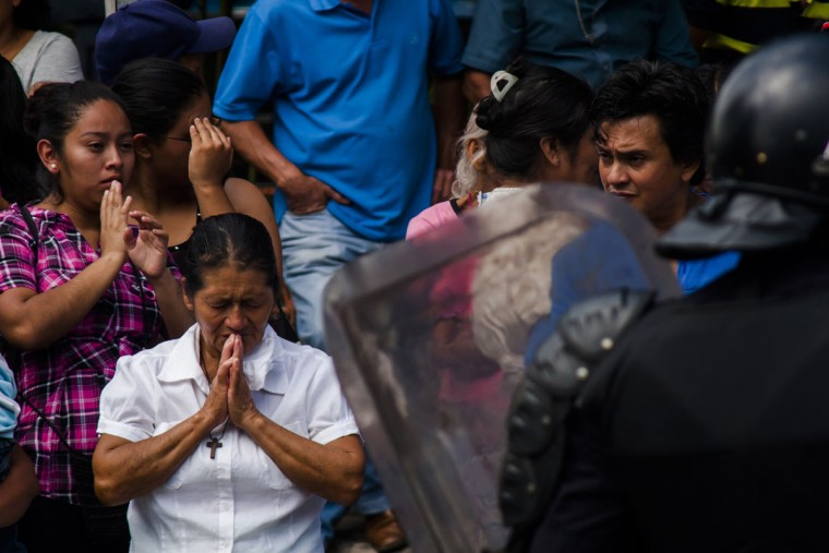 A relative of an inmate prays as more than a thousand inmates in buses ride out of the Cojutepeque prison in El Salvador, Thursday, June 16, 2016. This prison, which houses more than a thousand 18th street imprisoned gang members, will be closed down by the government, since it has been unable to prevent the amount of illegal activities happening inside the prison walls. Inmates will be relocated to other medium-security prisons. (AP Photo/Salvador Melendez)