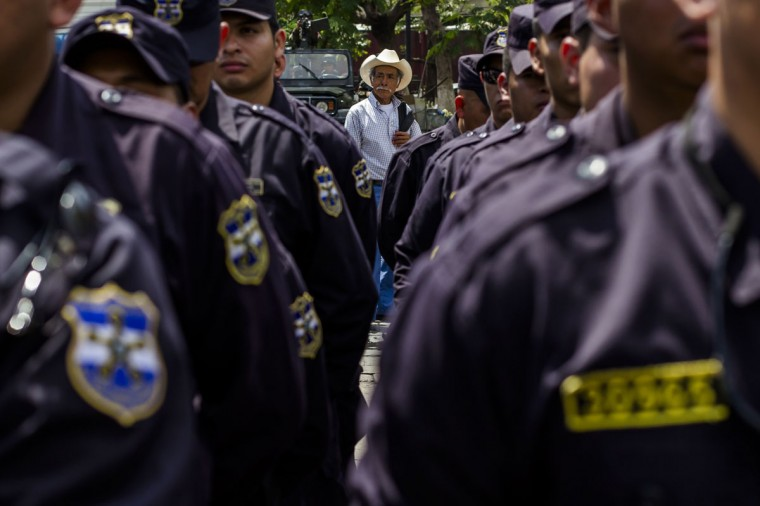 In this June 14, 2016 photo, a man looks at a formation of police and soldiers during a presentation to the press in the Central Square in San Salvador, El Salvador. After becoming the world's murder capital last year and posting an equally bloody start to 2016, El Salvador has seen its monthly homicide rates fall by about half. The government attributes the drop to a tough military crackdown on the country's powerful gangs, while the gangs themselves claim credit for a nonaggression pact between the three biggest criminal groups. (AP Photo/Salvador Melendez)