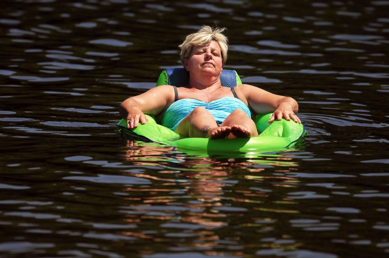 "Patti Glessner, 52, of Cambridge, Md., relaxes on her raft at Keen Lake in Canaan Township, Pa. The high pressure system, sometimes called a ""heat dome,"" will push conditions to their hottest point so far this summer, though record hot temperatures are not expected, according to the National Weather Service. (Butch Comegys/The Times & Tribune via AP)"