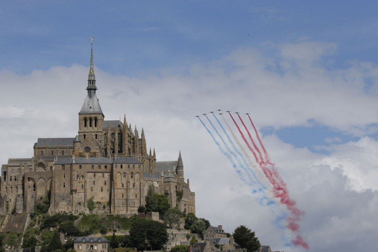 Jets with the Patrouille de France fly over the Mont-Saint-Michel prior to the start of the first stage of the Tour de France cycling race over 188 kilometers (116.8 miles) with start in Mont-Saint-Michel and finish in Utah Beach, France, Saturday, July 2, 2016. (AP Photo/Christophe Ena)