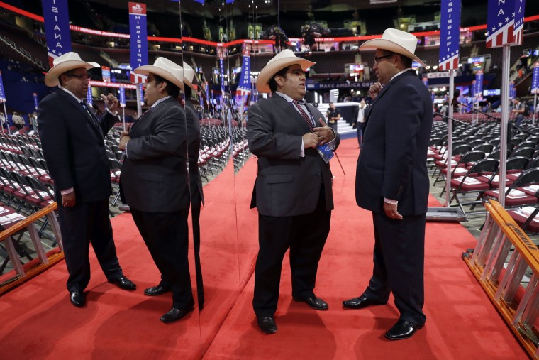 Texas delegates Artemio Muniz from Houston and Mark Gonzales from Dallas talk on the convention floor before first day of the Republican National Convention in Cleveland, Monday, July 18, 2016. (AP Photo/Matt Rourke)